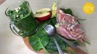 Een houten snijplank met spinaziebladeren waarop een glas groene smoothie staat, lepel en vork, een halve appel, plakjes avocado en enkele spek-avocado rolletjes