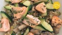 Een closeup van stukjes gebakken zalmmoot besprenkelt met takjes dille op een ondergrond van geroerbakte courgette met quinoa