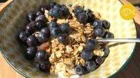 Een bord gevuld met geitenyoghurt met daarin notenmuesli en blauwe bessen.