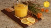 een glas sinaasappelsap op een snijplank met twee schijfjes citroen